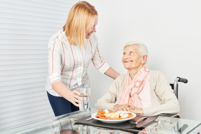 nursing lady serves a meal to a senior woman