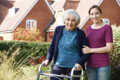 caregiver and a senior woman outside the house